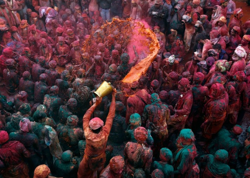 A man throws colored water on a crowd of people in India. (Photo credit: Ahmad Masood)